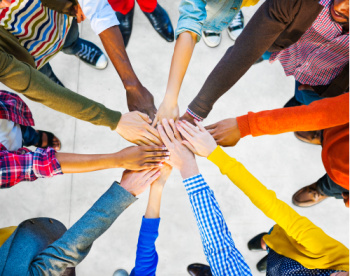 The benefits of tithing can include improving relationships and creating new relationships.  Here, people put their hands in a circle.