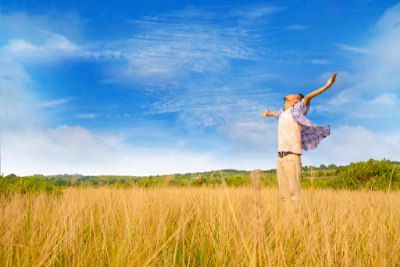 Man rejoicing in a field with arms outstretched.  This is the experience you can have after doing a forgiveness prayer and releasing resentments.