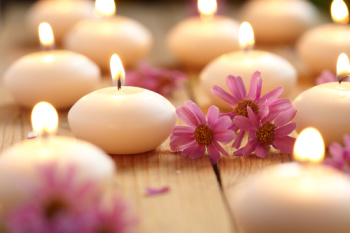 Candles and flowers creating a relaxing ambiance.  Many people feel very relaxed after a Reiki spiritual healing session.