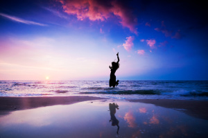 Tithe and Offering:  a feeling of joy can be encapsulated in tithing as symbolized by the happy person jumping on the beach.