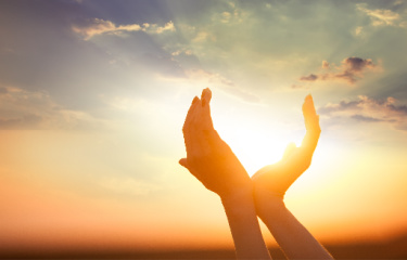 Tithe Offering:  Hands outlining the sun as if they are holding the sun.  The photo can also symbolize receiving a gift.