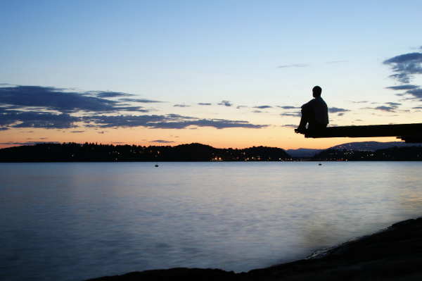 If you know the tithing definition, the question becomes why would you tithe?  The question is symbolized, here, by a photo of a man sitting at the end of a dock during sunset.