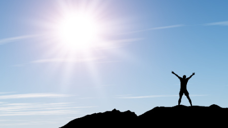 Man standing on a mountain greeting the sun.  This photo represents how vibrational energy healing can leave a person feeling refreshed.